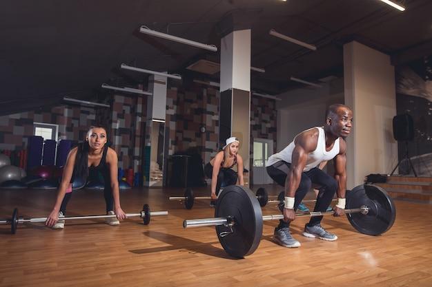 Leute, die kreuzheben mit schweren hanteln im fitnessstudio machen.
