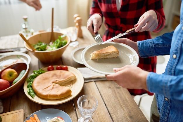 Leute, die kuchen am esstisch servieren
