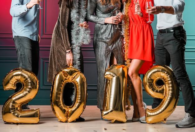 Leute, die mit inschrift 2019 von den ballonen stehen