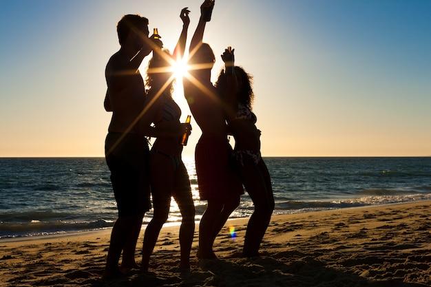 Leute, die party am strand mit getränken haben