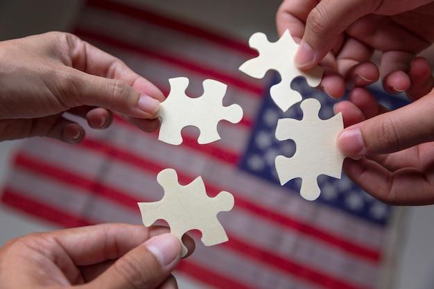 Leute, die puzzle zusammenbauen und teamunterstützung mit amerika-staatsflagge darstellen.
