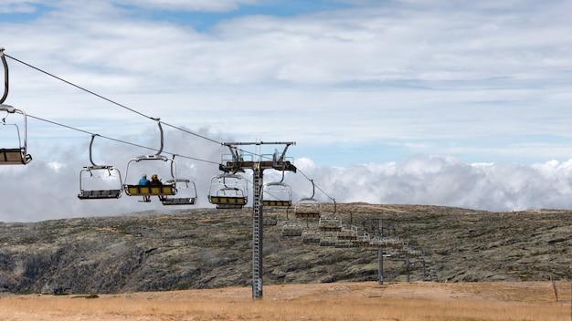 Leute, die sessellifte auf skistationen fahren, die berge und den horizont beobachten, zurück