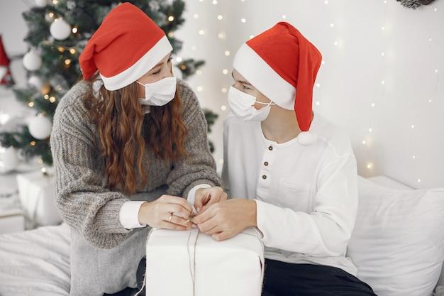 Leute, die sich auf weihnachten vorbereiten. coronavirus-thema. mutter spielt mit ihrem sohn. junge in einem weißen pullover.