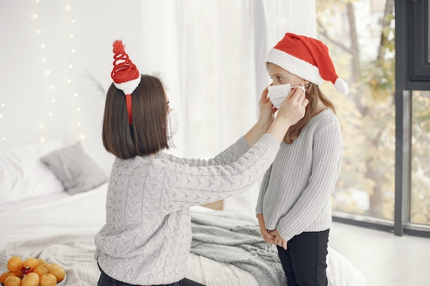 Leute, die sich auf weihnachten vorbereiten. coronavirus-thema. mutter spielt mit ihrer tochter. kind in einem grauen pullover.