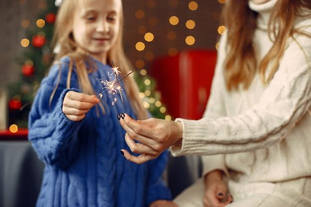 Leute, die sich auf weihnachten vorbereiten. kind mit bengalischen lichtern. die familie ruht sich in einem festlichen raum aus. kind in einem blauen pullover.