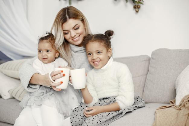 Leute, die sich auf weihnachten vorbereiten. mutter spielt mit ihren töchtern. die familie ruht sich in einem festlichen raum aus. kind in einem pullover pullover.