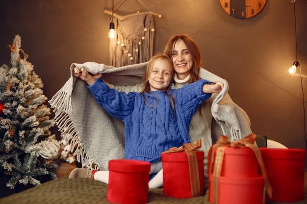 Leute, die sich auf weihnachten vorbereiten. mutter spielt mit ihrer tochter. die familie ruht sich in einem festlichen raum aus. kind in einem blauen pullover.