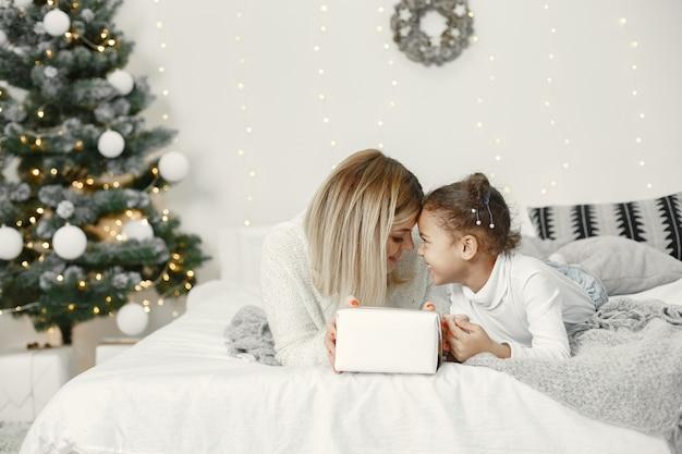 Leute, die sich auf weihnachten vorbereiten. mutter spielt mit ihrer tochter. die familie ruht sich in einem festlichen raum aus. kind in einem pullover pullover.