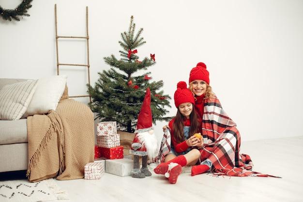Leute, die sich auf weihnachten vorbereiten. mutter spielt mit ihrer tochter. die familie ruht sich in einem festlichen raum aus. kind in einem roten pullover.