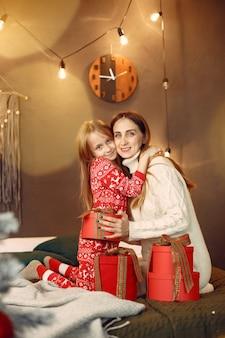 Leute, die sich auf weihnachten vorbereiten. mutter spielt mit ihrer tochter. die familie ruht sich in einem festlichen raum aus.