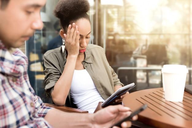 Leute, die sich ernsthaft auf smartphone beim sitzen in der kaffeestube konzentrieren