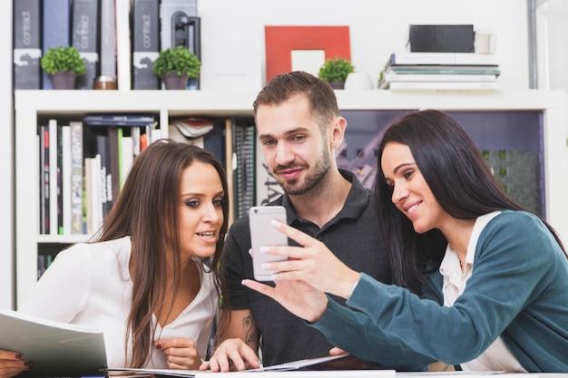 Leute, die smartphone im büro überwachen