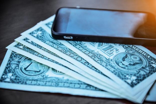 Leute, die smartphone verwenden, um online durch internet, smartphone und us-dollar auf hölzernem für das einkaufen oder die einsparung und die investition zu kaufen