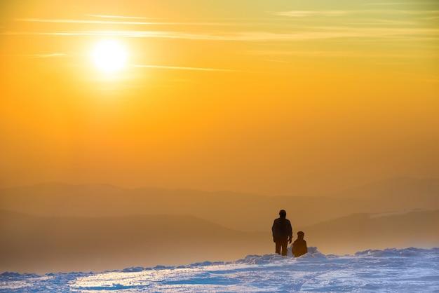 Leute, die sonnenuntergang in den winterbergen betrachten, die mit schnee bedeckt sind