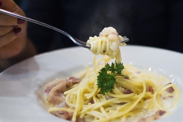 Leute, die spaghetti carbonara essen