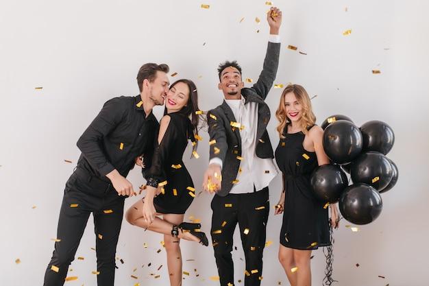 Leute, die spaß auf der party mit schwarzen luftballons und konfetti haben