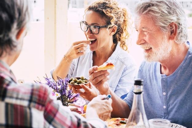Leute, die spaß haben und am esstisch zu mittag essen. verbringen sie zeit mit familie und freunden. liebevolle glückliche familie mit mehreren generationen, die zusammen essen und getränke genießt