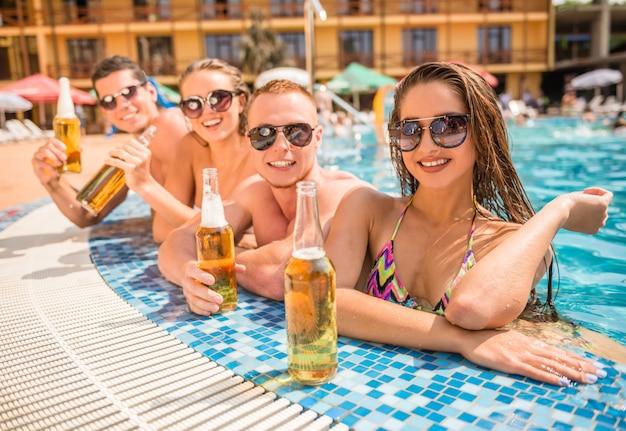 Leute, die spaß im swimmingpool lächelt und trinkt bier haben