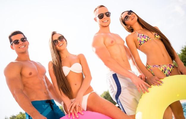 Leute, die spaß im swimmingpool mit farbigen gummiringen haben