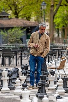 Leute, die traditionelles übergroßes straßenschach im parc des bastions spielen. genf, schweiz