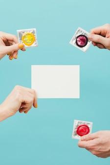 Leute, die verschiedene kondome und eine leere karte halten