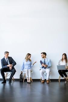 Leute, die vor einem interview im wartezimmer sitzen