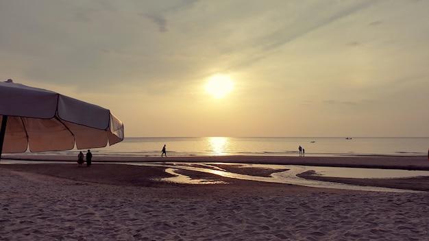 Leute, die während des sonnenaufgangs am strand spazieren gehen