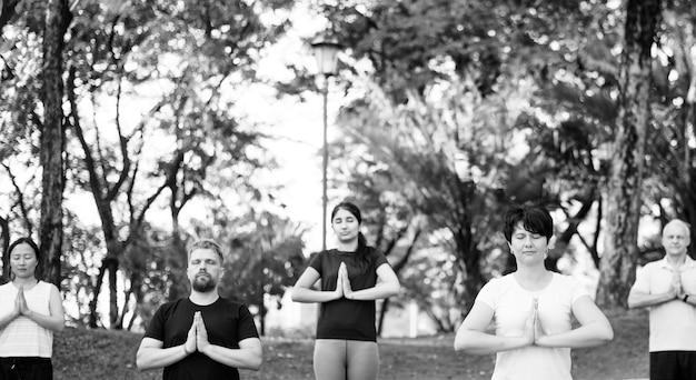 Leute, die yoga am park tun