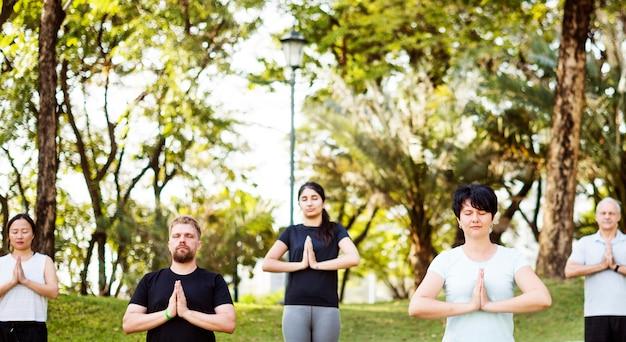 Leute, die yoga im park tun