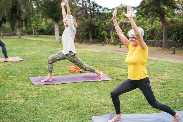 Leute, die yoga-kurse im freien im stadtpark machen - hauptaugenmerk auf das gesicht der älteren frau