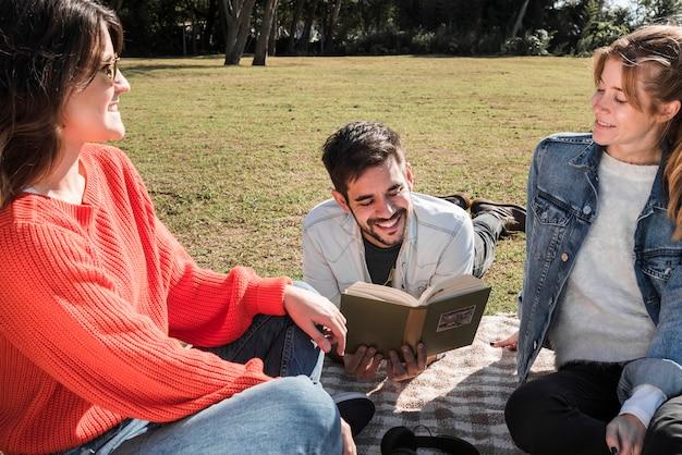 Leute, die zeit auf bettdecke im park verbringen