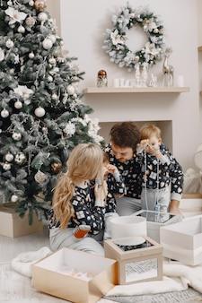 Leute, die zu weihnachten reparieren. leute, die mit kind spielen. die familie ruht sich in einem festlichen raum aus.