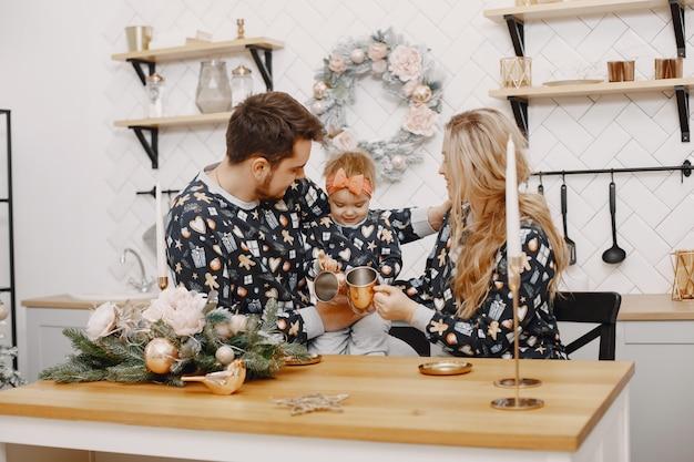 Leute, die zu weihnachten reparieren. leute, die mit tochter spielen. die familie ruht sich in einer festlichen küche aus.