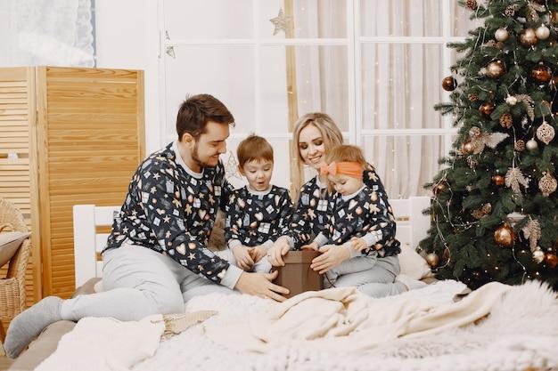 Leute, die zu weihnachten reparieren. leute sitzen auf einem bett. die familie ruht sich in einem festlichen raum aus.