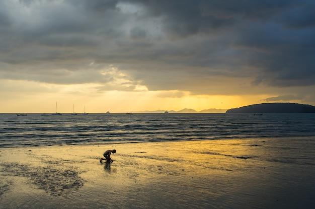 Leute entspannen sich und gehen am ao nang strand vor dem sonnenuntergang