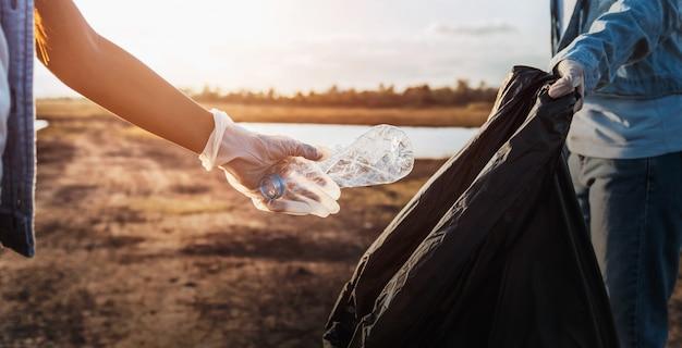 Leute erbieten sich freiwillig, abfallplastikflasche in schwarze tasche am park nahe fluss im sonnenuntergang zu halten