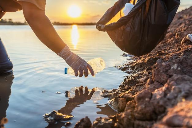 Leute erbieten sich freiwillig, abfallplastikflasche in schwarze tasche auf fluss im sonnenuntergang zu halten