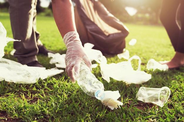 Leute erbieten sich freiwillig, plastikflasche des abfalls in schwarze tasche zu halten