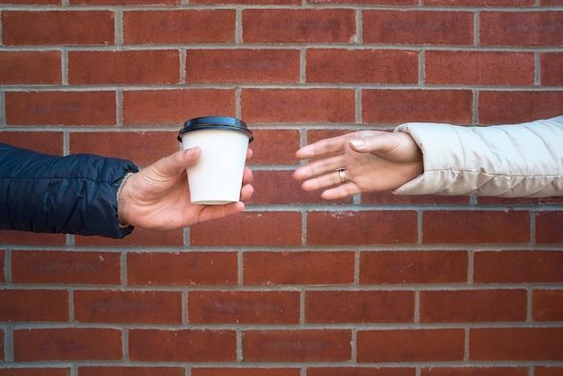 Leute-, getränke- und sorgfaltkonzept - nah oben von der männlichen und weiblichen hand, die einen tasse kaffee von einem mann nimmt