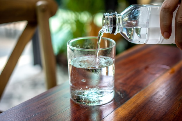 Leute gießen wasser in das glas