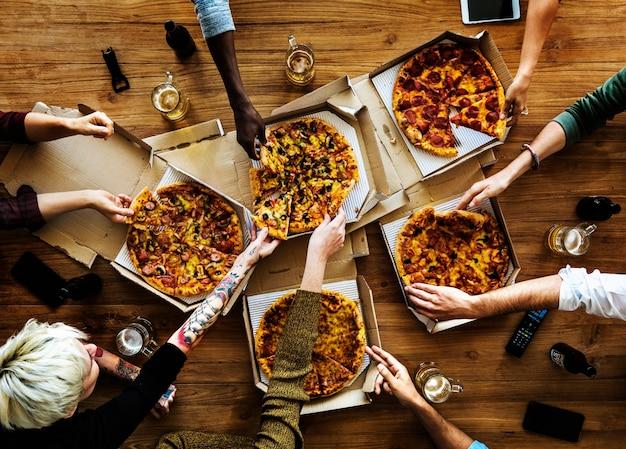 Leute-hände, die scheibe der pizza greifen