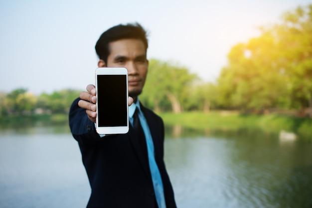 Leute halten das intelligente mobiltelefon, das den leeren schirm zeigt