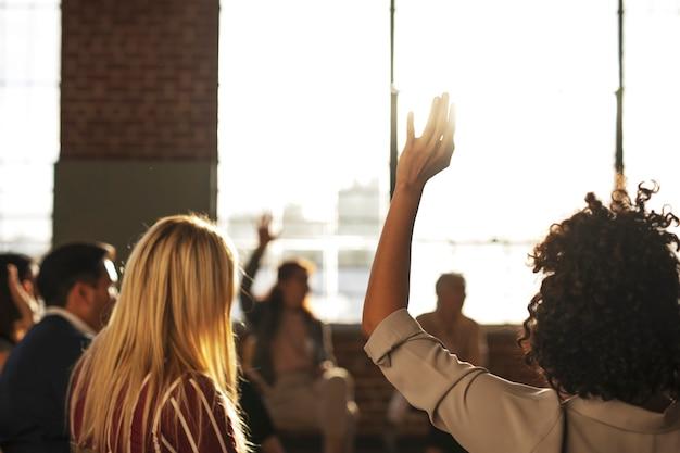 Leute hoben ihre hand in einem meeting