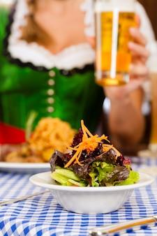 Leute im traditionellen bayerischen tracht, das im restaurant oder in der kneipe isst