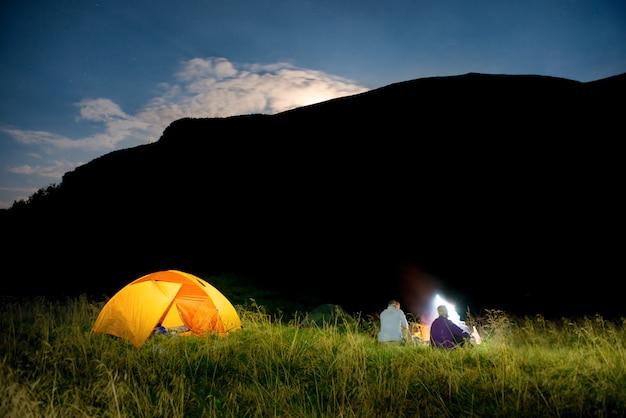 Leute in der nähe von beleuchtetem orangefarbenem zelt in einem campingplatz nachts mit berg und steigendem mond