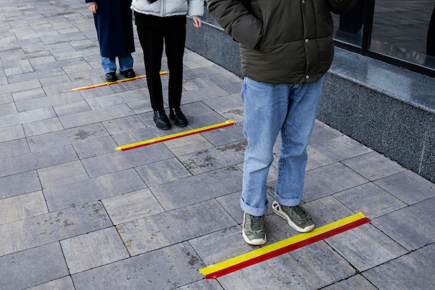 Leute in der schlange, die hinter dem sozialen distanzstreifen warten