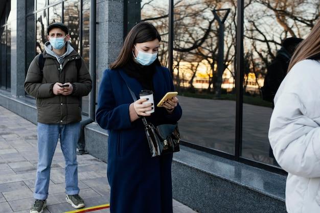 Leute in der schlange, die masken tragen