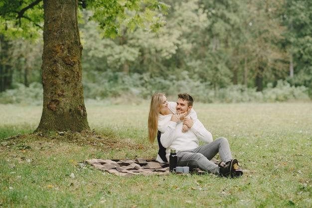 Leute in einem park. frau in einem braunen mantel. mann in einem weißen pullover. paar in einem picknick.
