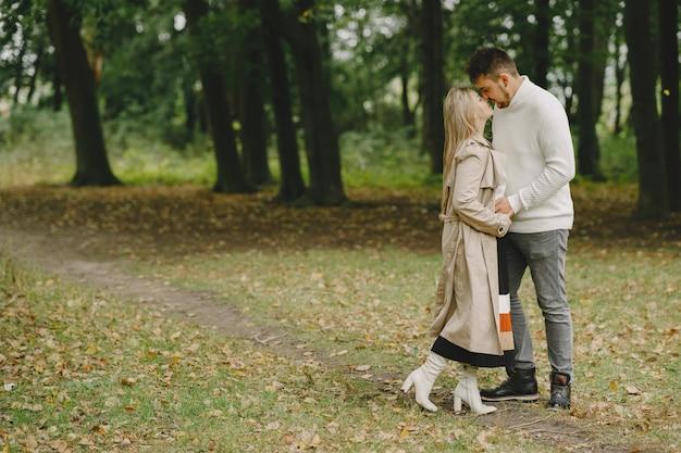Leute in einem park. frau in einem braunen mantel. mann in einem weißen pullover.
