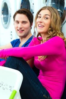 Leute in einem waschsalon, die ihre schmutzige wäsche waschen, vor waschmaschinen sitzen und miteinander reden